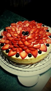 Cheesecake with a sour cream icing, strawberries and blueberries.